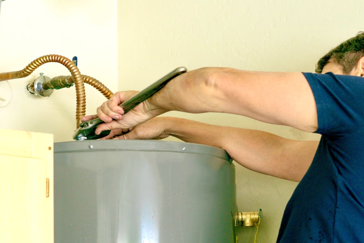 adult-male-tightening-water-line-connection-to-a-hot-water-heater-during-installation-home_t20_0XOgpw